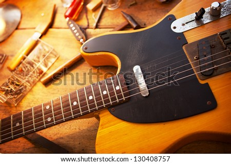 guitar on guitar repair desk vintage electric guitar on a guitar repair work shop single. Black Bedroom Furniture Sets. Home Design Ideas