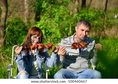 Guy and girl holds kebab skewer and wants to eat