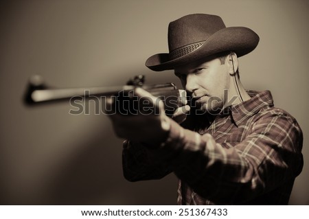 guy in a hat with a gun. cowboy style. portrait.
