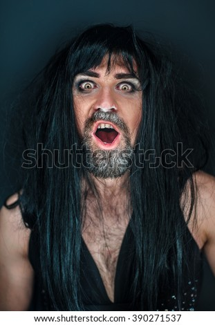 guy in a wig with a beard, wearing a dress seduces