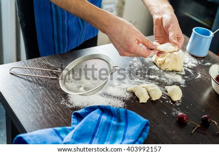 guy in his kitchen preparing dumplings with cherries.He uses a bottle instead of a rolling pin