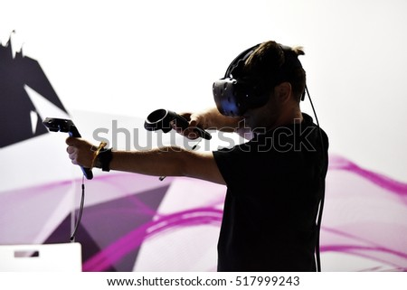 Guy playing with virtual reality headset and hand controls