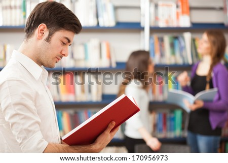 Guy reading a book in a library