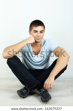 Guy sitting on floor in room
