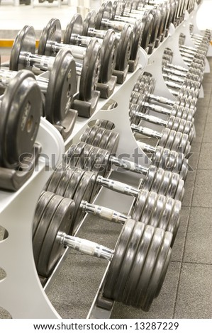 Gym or gymnasium equipment in a world-class facility suitable for athletes training for international events. Picture shows a row of dumbbells neatly stacked on their stands.