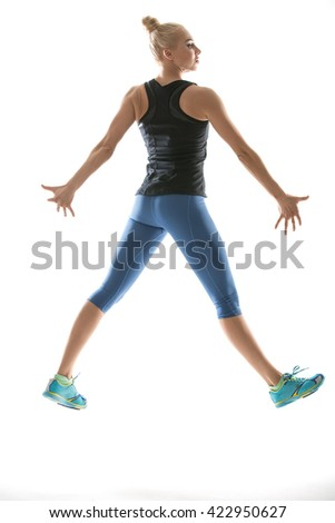 Gymnast blonde girl in the sportswear jumps on the white background in the studio. She wears cyan-yellow sneakers, mint socks, blue pants and black sleeveless t-shirt. Her hands are on the sides of