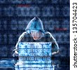 Hacker typing on a laptop with binary code in background - stock photo