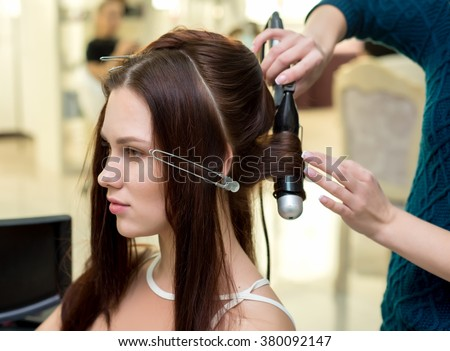 Hair stylist making ringlets to brunette woman. Hairdresser working with beautiful woman hair in hairdressing salon. Close up view of hand, curling iron and the appliance