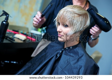 hair stylist using dryer on woman wet hair in salon