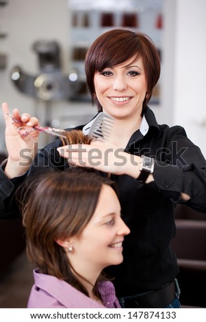 Hairdresser cutting a womans hair in a professional salon with both women smiling happily