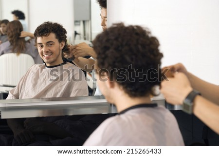 Hairdresser cutting man's hair in salon, reflection in mirror, smiling, rear view, portrait