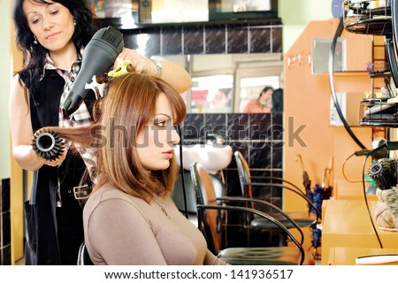 hairdresser dries hair in a hair salon