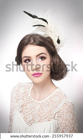 Hairstyle and make up - beautiful young girl art portrait. Genuine natural brunette with creative haircut, studio shot. Attractive female with beautiful lips and eyes in white lace blouse, over white