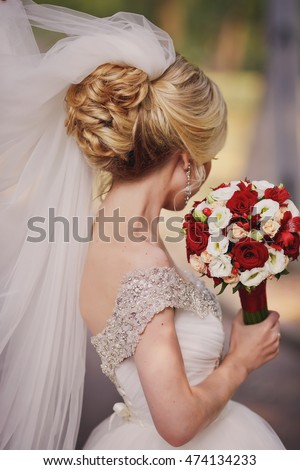 hairstyle beautiful blonde bride with red bouquet of flowers