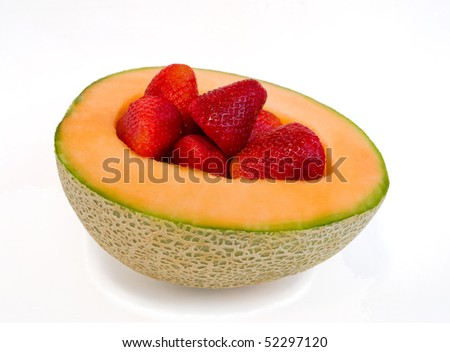 half a cantaloupe with fresh strawberries, isolated on white