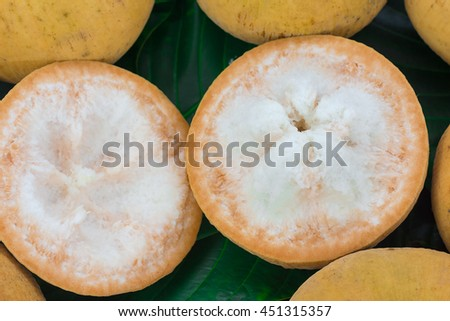 Half cut santol fruit on green leaf background.