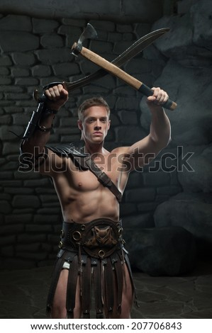 Half length portrait of young attractive warrior gladiator with muscular body holding sword and axe on dark background. Concept of masculine aggressive power, strength