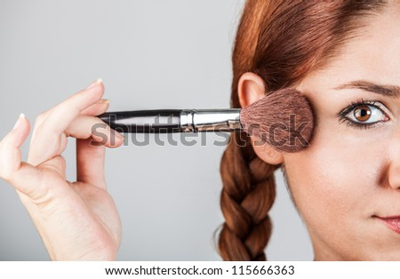 half of face portrait of a woman putting on makeup with a blush brush
