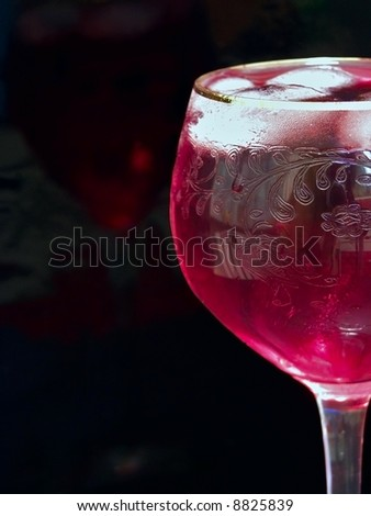 Half of wineglass full of red wine with ice
