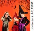 Halloween group of children girls costumes on orange background [Photo Illustration] - stock photo
