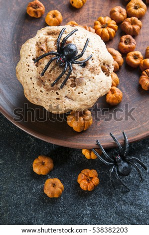 Halloween holiday background with treats and decor - cupcake decorated with little pumpkins candies and spiders on  plate