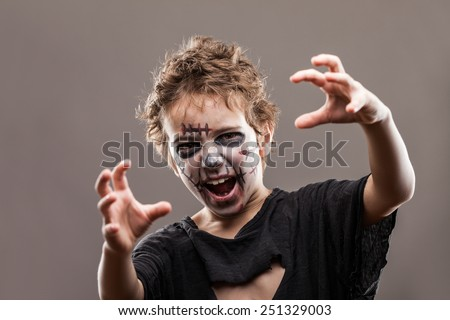 Halloween or horror concept - screaming walking dead zombie child boy reaching hand