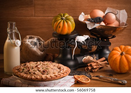 Halloween pumpkin pie with spiders and mice in rustic setting