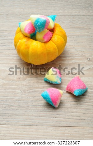 Halloween pumpkin that is hollowed out and filled with multiple sweets and candies, composition over a wooden background