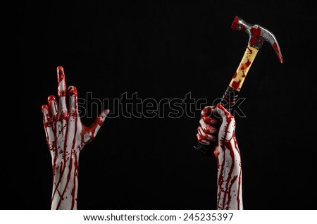 halloween theme: bleed hand holding a bloody hammer isolated on a black background