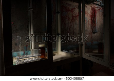 Halloween theme blood of stained laboratory with test tubes holder and other medicine devices inside with blood spattered wall in dark room