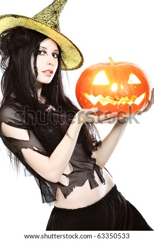 Halloween witch holding carved pumpkin, isolated over white background.