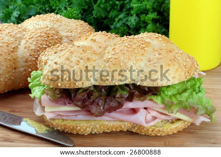 Ham, cheese, lettuce and mustard sub sandwich on a cutting board.  Parsley, a sub roll, and mustard as a backdrop.  Close-up, macro appetizing view.