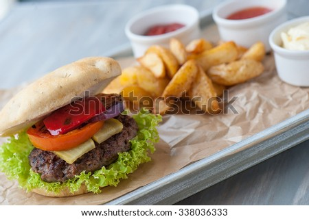 hamburger with baked potatoes and three sauces