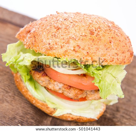 Hamburger with fried onion, tomatoes, iceberg lettuce on a wooden board