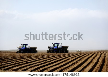 Hamer, Idaho, USA May 11,. 2009 Farm machinery working in the field plowing and planting potatoes.