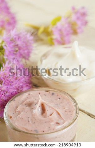 hand and face cream with pink flowers on bright, rusty wooden