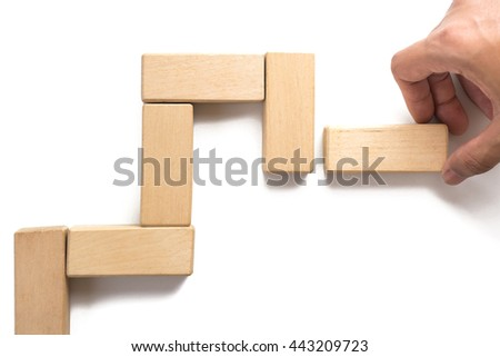 Hand arranging wood block stacking as step stair can use for presentation template or bullet or infographics.