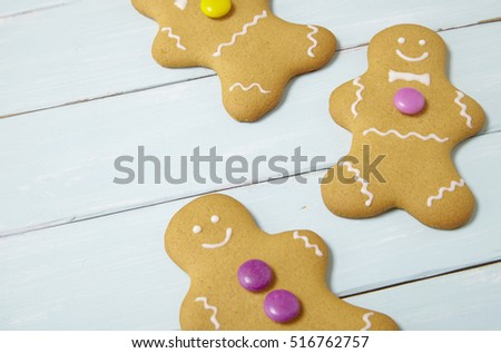 Hand decorated gingerbread men on a painted wooden table background with blank space at side