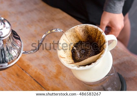 Hand drip coffee , Barista pouring water on coffee ground with filter