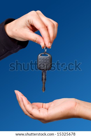 Hand giving a key over blue sky