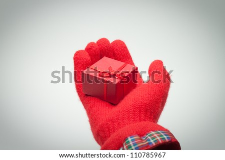 hand giving red box with present over grey