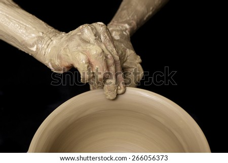 Hand hold brim of clay bowl at potters wheel