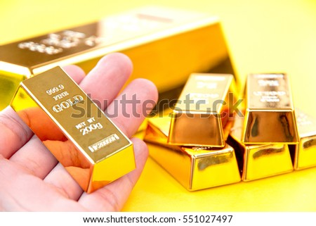 Hand hold gold bars