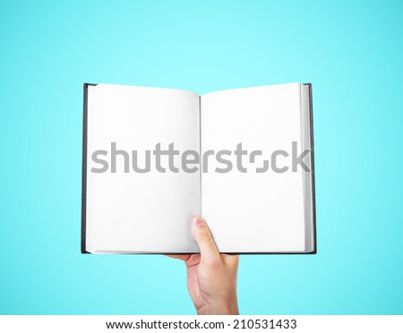 hand holding a blank book on a blue background