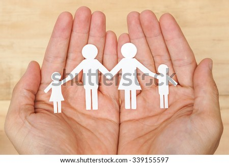 Hand holding a cutout paper chain family
