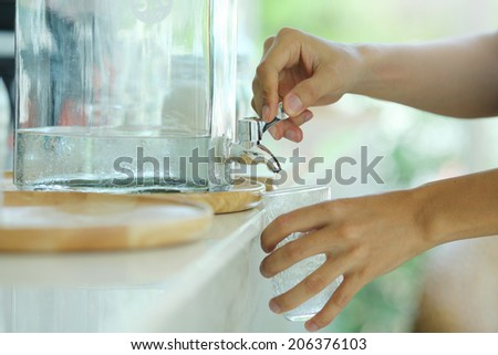 Hand holding a glass of water poured faucet