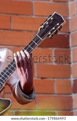 Hand holding a guitar neck with Brick background