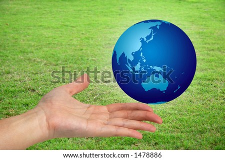 Hand holding a the world with a green grassy field in the background