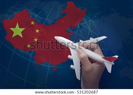hand holding airplane with map of China.