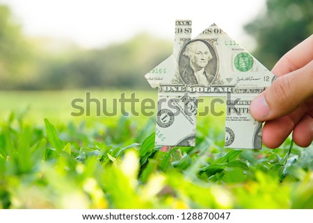Hand holding banknote house icon,real estate concept.